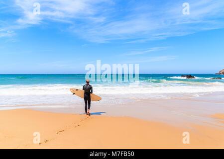 PRAIA DO AMADO BEACH, PORTUGAL - MAY 15, 2015: Surfer walking on Praia do Amado beach with ocean waves hitting shore. - Stock Photo