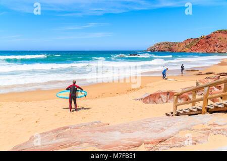 PRAIA DO AMADO BEACH, PORTUGAL - MAY 15, 2015: People surfing on Praia do Amado beach with ocean waves hitting shore. - Stock Photo