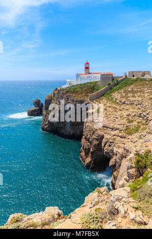 Blue sea and lighthouse on top of cliff at Cabo Sao Vicente, Algarve region, Portugal - Stock Photo