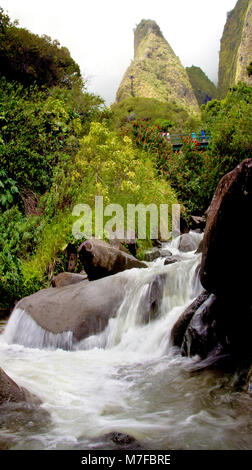 Tourists crossing bridge under the Maui Iao Needle with Iao Stream in the foreground at Iao Valley State Park, Maui, - Stock Photo