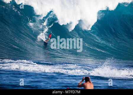 A tow-in surfer drops down the face of Hawaii's big surf at Peahi (Jaws) off Maui, Hawaii.