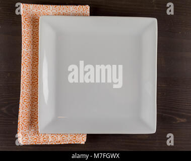 Empty Square Plate and Orange Napkin on dark wooden background - Stock Photo
