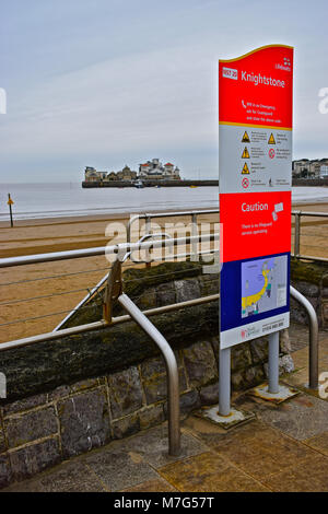 Warning Sign overlooking the beach at Weston-super-Mare with the historic Knightstone Island in the background. - Stock Photo