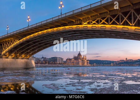 A span of the Margaret Bridge in Budapest with ice floes on the Danube and Parliament in the background - Stock Photo