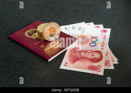 Chinese passport with Yuan banknotes and bitcoins - Stock Photo