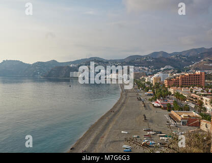 Almunica Beach and waterfront in Andalucia, Spain. Some people sit on the Beach to watch the Sun going down over - Stock Photo