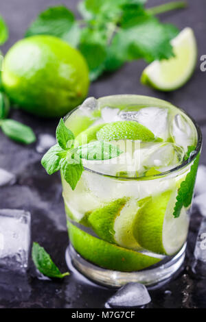 Cold refreshing summer drink with lime, mint and ice cubes in a glass on a dark stone background. Mojito. Lemonade. - Stock Photo