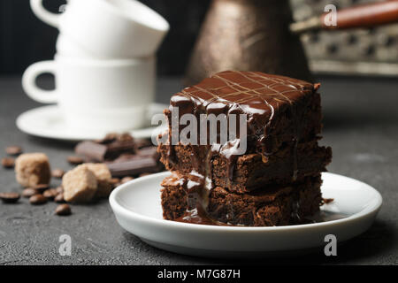 Delicious homemade brownie with chocolate sauce and caramel on the table. Selective focus - Stock Photo