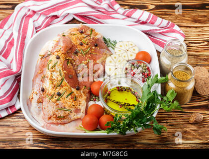 Fresh raw meat. Lamb with spices - rosemary, juniper, garlic and tomatoes in a white ceramic form on a wooden table. - Stock Photo