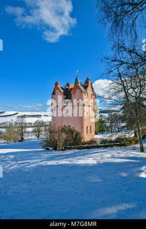 CRAIGIEVAR CASTLE ABERDEENSHIRE SCOTLAND  PINK TOWER BLUE SKY AND WINTER SNOW ON THE SURROUNDING FIELDS AND HILLS - Stock Photo
