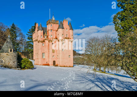 CRAIGIEVAR CASTLE ABERDEENSHIRE SCOTLAND A BLUE SKY AND FOOTPRINTS LEAD TOWARDS THE PINK TOWER SURROUNDED BY FIR - Stock Photo