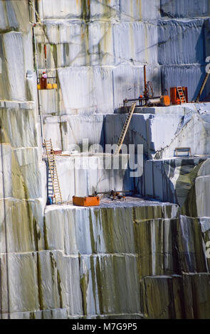 Workmen stand close to the edge of a steep and dangerous drop as they cut granite blocks at the Rock of ages Quarry - Stock Photo