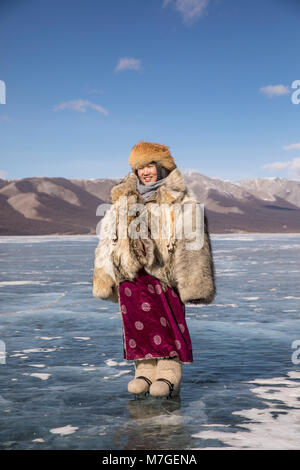 young Mongolian lady in wolfskin jacket on a frozen lake Khovsgol in northern Mongolia - Stock Photo