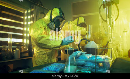 In the Underground Laboratory Two Clandestine Chemists Wearing Protective Coveralls and Masks Cook Drugs. They Work with Beakers, Distillation.