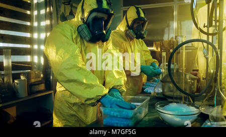 In the Underground Laboratory Two Clandestine Chemists Wearing Protective Masks and Coveralls Pack Bags of Synthesised Crystal Meth into Boxes