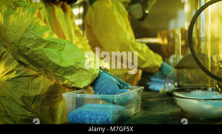 In the Underground Laboratory Two Clandestine Chemists Pack Bags of Drugs into Boxes. Laboratory is Full of Illegal Equipment. They Pack Meth.