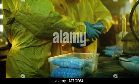In the Underground Laboratory Two Clandestine Chemists Pack Bags of Drugs into Boxes. Laboratory is Full of Illegal Equipment. They Cook Meth.