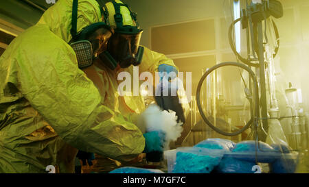 In the Underground Drug Laboratory Two Clandestine Chemists Mix Chemicals while Cooking Narcotics. They Use Canisters and Beakers, Toxic Compounds.