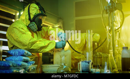 In the Underground Drug Laboratory Two Clandestine Chemists Wearing Protective Masks and Coveralls Use Hosepipe For Drug Distillation. They Cook Meth.