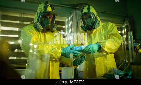 In the Underground Laboratory Two Clandestine Chemists Pack Bags of Drugs into Boxes. Laboratory is Full of Glassware and Other Narcotics Products