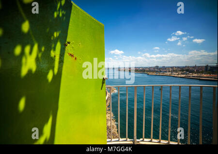 View over the harbor of Havana, Cuba, from the lighthouse at El Morro seen through a bright green doorway - Stock Photo