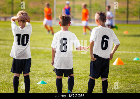Children Football Team. Young Boys Watching Soccer Match. Football Tournament Competition in the Background. KidsFootball - Stock Photo