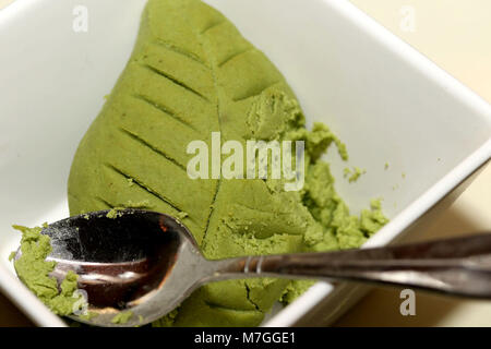 Green Wasabi leaf in white bowl with spoon - Stock Photo