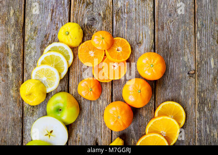 sliced citrus mix lemon grapefruit lime and orange in geometrical shapes on dark wood rustic background soft focus - Stock Photo