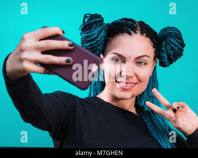 Portrait of young attractive hipster woman with dyed colorful african braids making selfie photo on smartphone isolated - Stock Photo