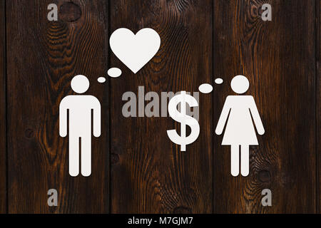 Paper couple, love vs money. Wooden background. Abstract conceptual image - Stock Photo