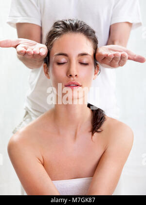 Pretty young woman receiving a head massage in beauty salon - Stock Photo