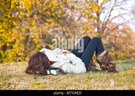 Beautiful girl with book sleeping on grass in the autumn colored park