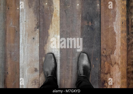 Businessman in black shoes standing on wooden floor - Stock Photo