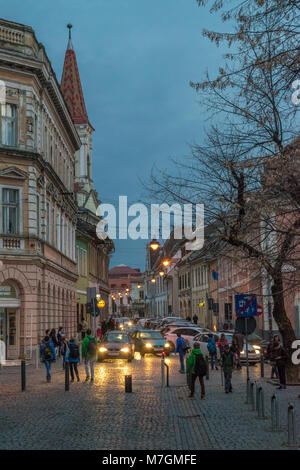 SIBIU, ROMANIA - 8 MARCH 2016: Chids waling down a street at sunset in Sibiu, Romania - Stock Photo