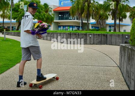 Young man on a skateboard carrying a bouquet of flowers to his  grandmother's birthday, Riverview Tavern in Douglas - Stock Photo