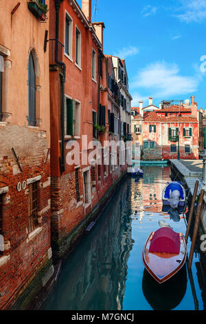 Boats on narrow canal along old brick houses in Venice, Italy ( vertical composition). - Stock Photo