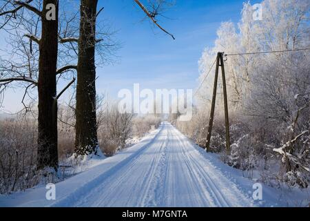 Snowbound road of Mazury District in Wegorzewo, Poland - Stock Photo