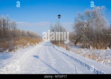 Snowbound boardwalk on Wegorapa river's bank in Wegorzewo, Mazury, Poland - Stock Photo