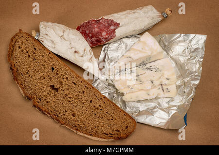 Breakfast theme still life. Bread, Roquefort cheese and smoked sausage on brown craft paper background - Stock Photo