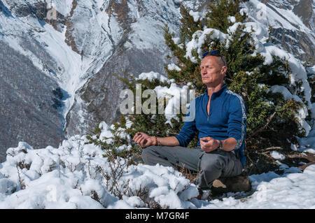 Meditating man in snowy Himalayan mountains - Stock Photo