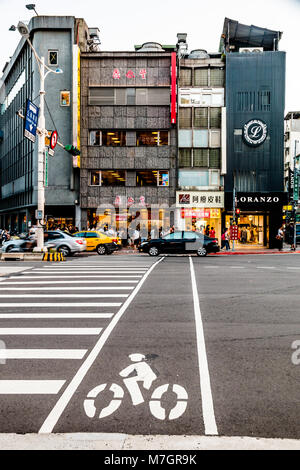 Zebra-crossing with bicycle lane on Xinyi Road in front of the original Din Tai Fung restaurant. Taken in August - Stock Photo