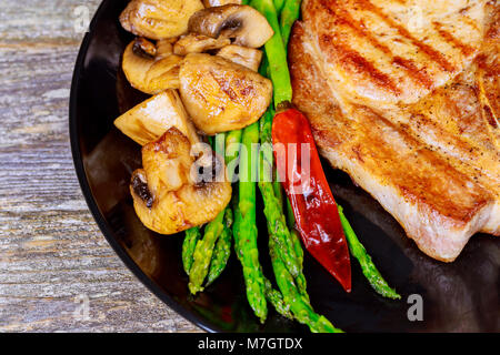 Grilled striploin sliced steak. Juicy thick grilled steak seasoned with asparagus and mushrooms fresh of the summer - Stock Photo