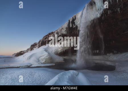 Frozen Seljalandsfoss waterfall in winter in south Iceland - Stock Photo