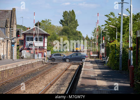 A Northern Rail pacer train departs  Parbold  (Lancashire) as the level crossing re opens to road traffic with cars - Stock Photo