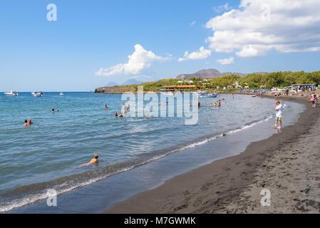 Vulcano Island, Italy - August 22, 2017: People relax on the black volcanic beach on Vulcano Island. - Stock Photo