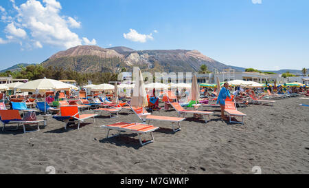 Vulcano Island, Italy - August 22, 2017: People relax on the black volcanic beach on Vulcano Island. - Stock Photo