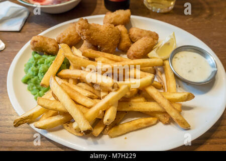 A plate of scampi, chips, mushy peas and tartar sauce. - Stock Photo