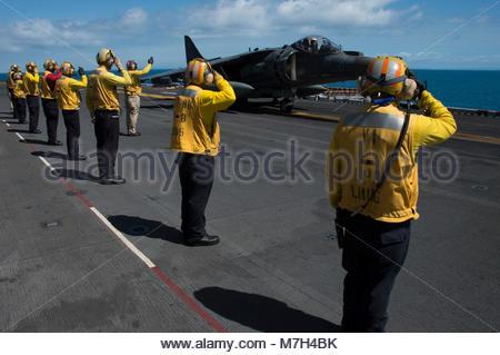 McDonnell Douglas (now Boeing) AV-8B Harrier. CORAL SEA (August 22, 2017) Sailors salute the pilot of an AV-8B Harrier - Stock Photo