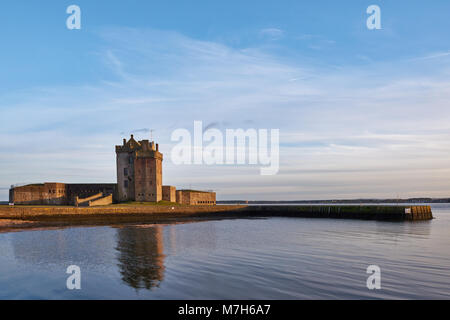 The Setting sun from the Tay Estuary reflects off the Fortified walls of Broughty Castle, near Dundee in Angus, - Stock Photo