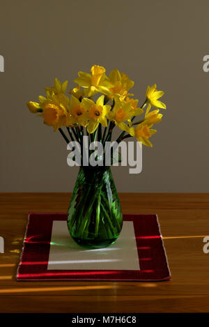 Yellow daffodils in a green vase on a table near a window. - Stock Photo